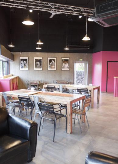 Comme à la maison BOUTIQUE à ANNECY, BOULANGERIE, vue sur l'espace dégustation avec une table d'hôte en bois vieilli, chaise Tolix, et toilettes pmr rose. Espace réalisé par le STUDIO frvr