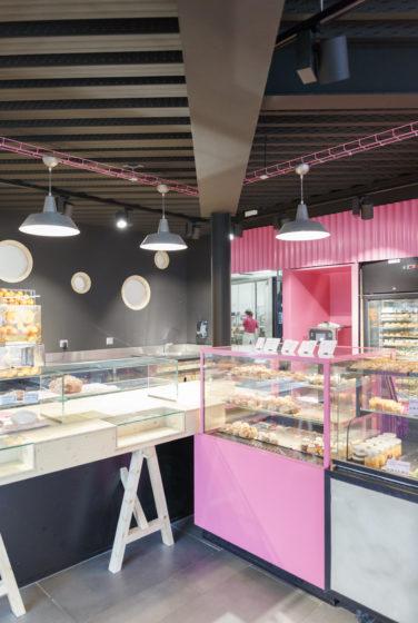 Comme à la maison BOUTIQUE à ANNECY, BOULANGERIE, vue sur l'espace boulangerie avec vitrine de présentation choux, hublot donnant sur le laboratoire, en tôle ondulé rose. Espace réalisé par le STUDIO frvr