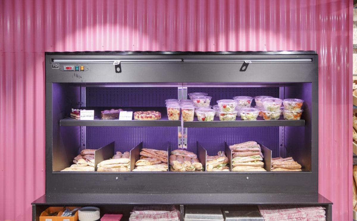 Comme à la maison Boutique à Annecy, boulangerie vue sur de détail sur la vitrine réfrigérée traiteur pour les sandwich et salades, laqué noir et encadré par une tôle rose, espace conçu par le studio frvr.