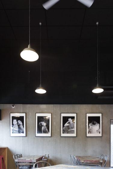 Comme à la maison Boutique à Annecy, boulangerie vue de détail sur les portraits noir et blanc sur un fond béton, plafond noir et luminaire acier, conçu par le studio frvr.