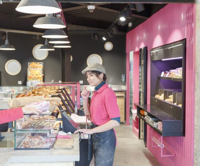 Comme à la maison boutique à Annecy, boulangerie vue sur vendeuse en uniforme, espace et meuble béton, acier et tôle rose, conçu par le studio frvr.
