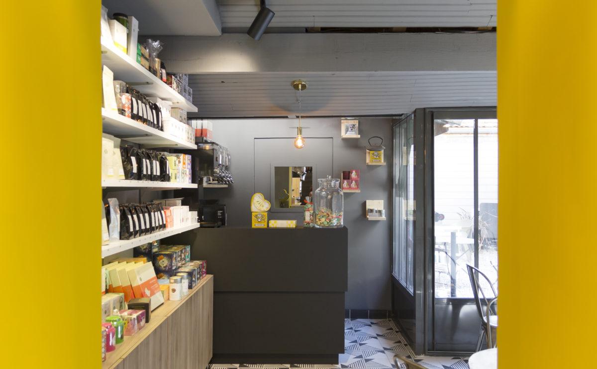 épicerie sur cours à Lyon, vue intérieur sur le salon de thé, mur jaune, étagère à thé, comptoir noir, ampoule suspendue. Conçu en collaboration, Pep's création et le studio frvr
