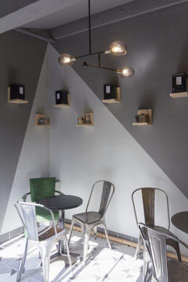 épicerie sur cours à Lyon, vue intérieur de l'espace salon de thé, avec peinture géométrique gris clair et foncé, étagère bois, chaise et table acier Tolix. Conçu en collaboration, Pep's création et le studio frvr