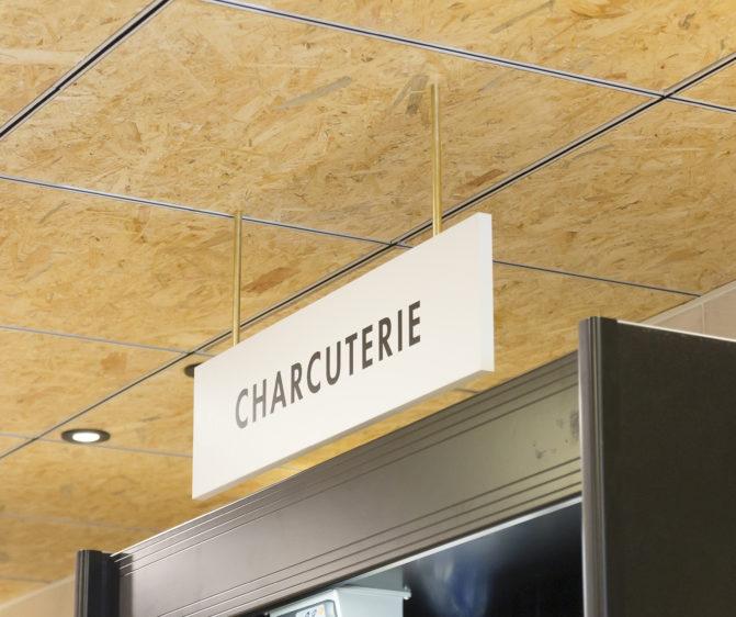 épicerie sur cours à Lyon, vue de détail sur la signalétique, plafond en bois triply, tube laiton, panneau blanc, texte noir, charcuterie. Conçu en collaboration, Pep's création et le studio frvr