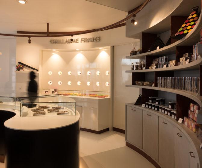 Pâtisserie Guillaume France à Lunel, vue générale avec vitrine centrale, mur à tablette chocolat, et étagère de produits sec confiture, biscuit, boutique conçue par l'agence de design frvr.