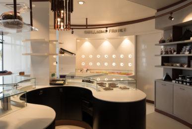 Pâtisserie Guillaume France à Lunel, vue générale avec vitrine centrale, mur à tablette chocolat, et étagère de produits secs conçue par l'agence de design frvr.