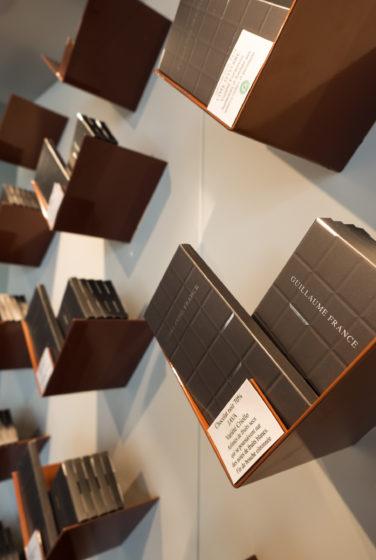 Pâtisserie Guillaume France à Lunel, vue en détail des tablettes de chocolat en libre service dans une structure en tôle acier laqué cuivre plié , boutique conçue par l'agence de design frvr.
