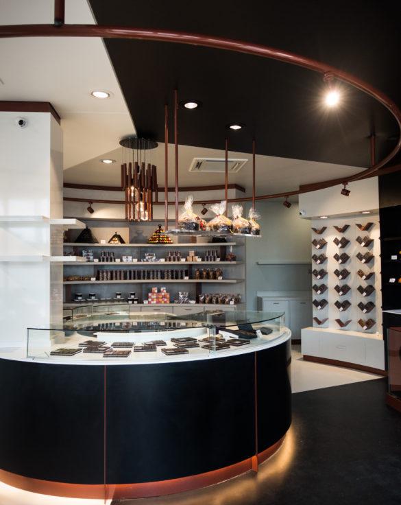 Pâtisserie Guillaume France à Lunel, vue générale avec vitrine centrale, mur à tablette chocolat, et étagère de produits sec confiture, biscuit, boutique conçue par l'agence lyonnaise de design frvr.
