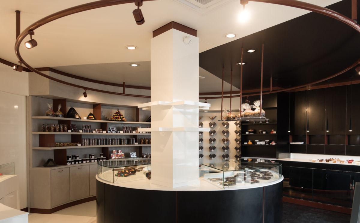 Pâtisserie Guillaume France à Lunel, vue générale avec vitrine centrale, mur à tablette chocolat, et étagère de produits secs, et vitrine pâtisserie individuelle, conçue à Lyon par l'agence de design frvrv.