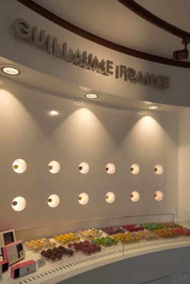 Pâtisserie Guillaume France à Lunel, vue en détail du mur macaron avec une présentation individuelle rétro éclairé, boutique conçue à Lyon par l'agence de design frvr.