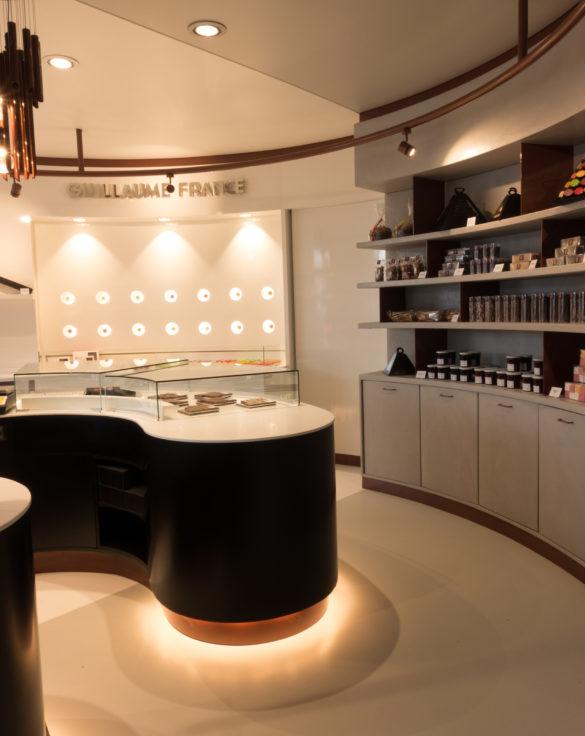 Pâtisserie Guillaume France à Lunel, détail du meuble revente stratifié gris et vue sur le mur macaron, boutique conçue par l'agence de design frvr.