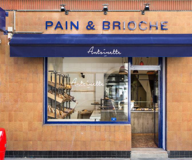 Façade boutique boulangerie Antoinette Pain et brioche, avec enseigne latéral drapeau rétro éclairé, studio frvr.