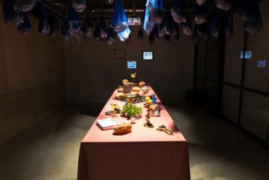 Scénographie soirée inauguration Antoinette pain et brioche vue générale avec mise en scène de la table et suspension de sac filet bleu et projection vidéo
