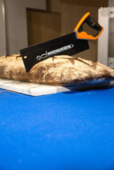 Scénographie soirée inauguration Antoinette pain et brioche détail sur coupe de pain à la scie à bois magnusson