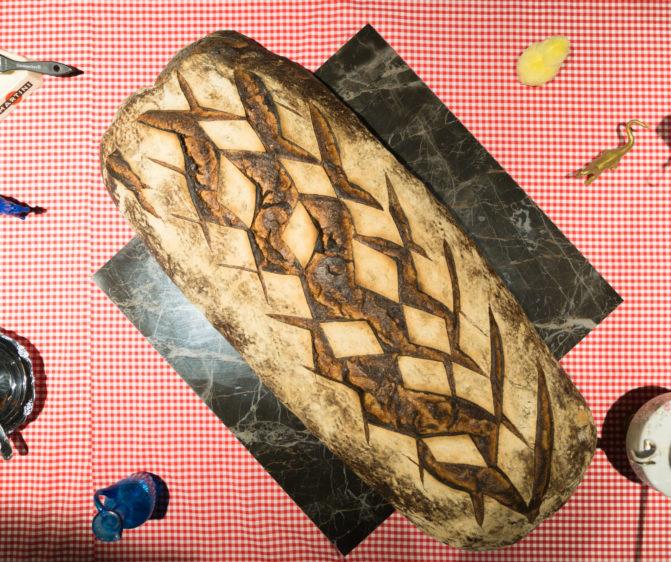 Scénographie soirée inauguration Antoinette pain et brioche détail d'un pain au levain sur marbre et nappe vichy